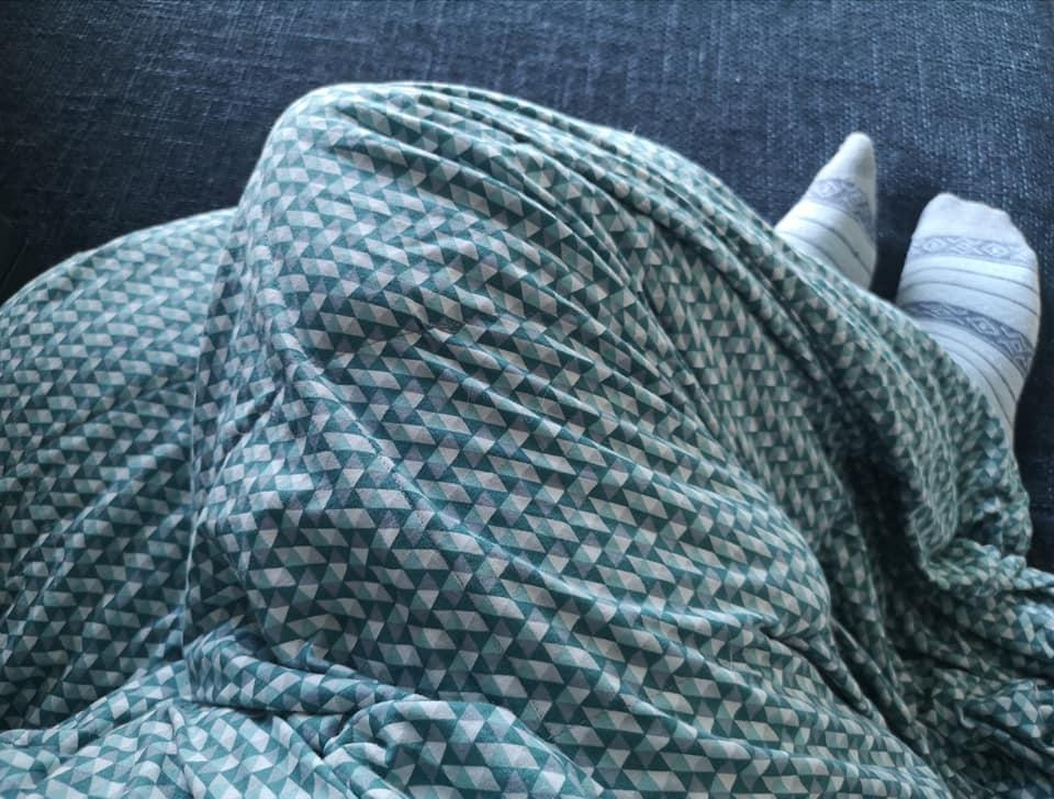 Ik zit op de bank onder mijn verzwaringsdeken, in de kleuren groen, grijs en wit.