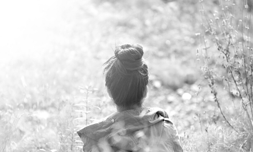 Foto van een vrouw die je van de achterkant ziet, met een knot in haar haar