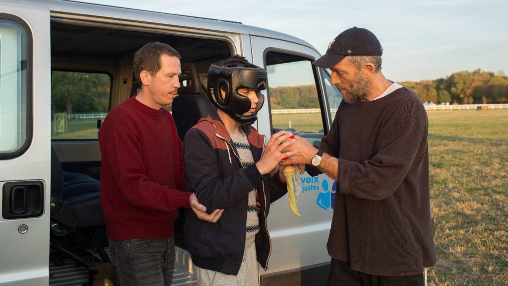 Filmstill uit Hors Normes. Bruno en Malik helpen een autistische jongen met een helm op uit de auto.