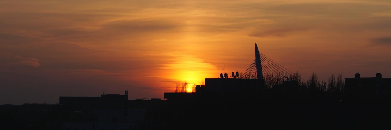 Foto van mijn uitzicht: skyline met Prins Clausbruf en daarachter de ondergaande zon.